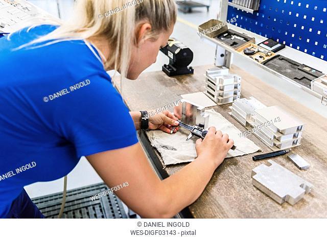 Woman measuring metal workpiece