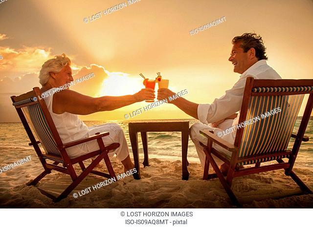 Senior couple toasting drinks on beach, Maldives
