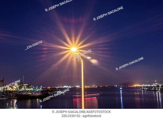 Lamppost illuminated above San Diego Harbor at night. San Diego, California, United States