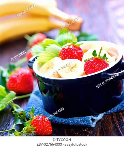 strawberry with bananas in bowl and on a table