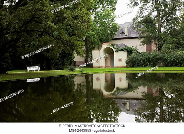 Baroque architectural style building reflected in the water canal in the Schwetzingen palace garden in late summer, Schwetzingen, Germany