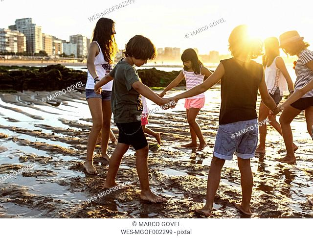 Kids playing hand in hand on the beach at sunset