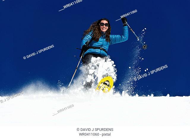 A woman having fun snowshoeing down a deep fresh snow field
