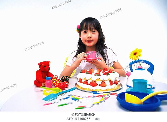 Little Girl holding a saucer and a cup While sitting at a table with a birthday cake and some kitchenware, looking at camera, Smiling, Front View