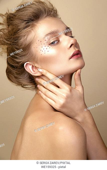 Studio Portrait of a young cute blonde model girl in art makeup with rhinestones