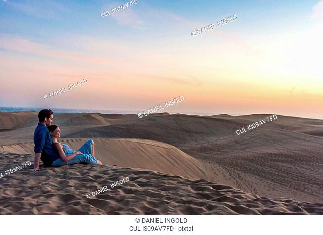 Romantic mid adult couple sitting on dunes, Maspalomas, Gran Canaria, Canary Islands, Spain