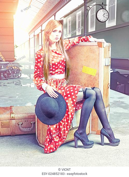 The girl sitting on the suitcase waiting at the retro railway station