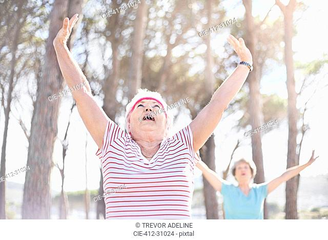 Senior woman stretching arms overhead in yoga class in sunny park