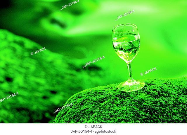 Glass of water beside stream
