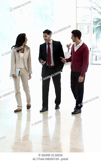 Business associates talking while walking together in office