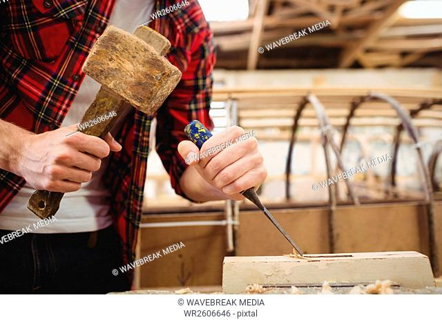 Man working over a wooden plank