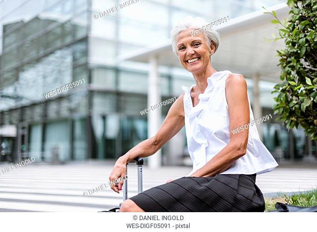 Portrait of happy senior woman with baggage sitting in the city