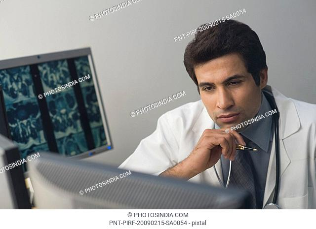 Male doctor examining an X-Ray report