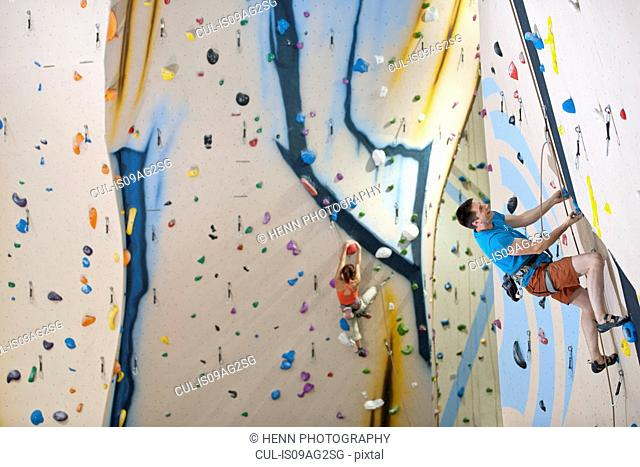 Man and woman climbing with ropes on climbing wall