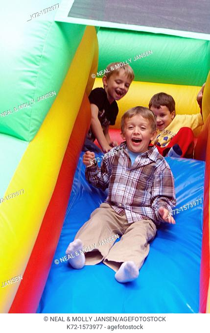 Little boys excited on slide on an inflatable ride