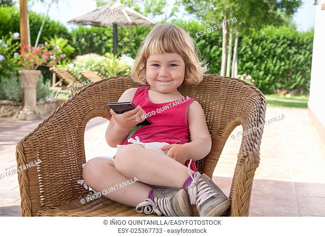 blonde caucasian girl two years old in summer red dress sitting on wicker chair with smartphone or mobile phone in her hand looking and smiling