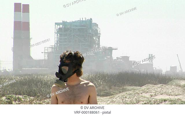 A man in a gas mask stands in front of a power plant