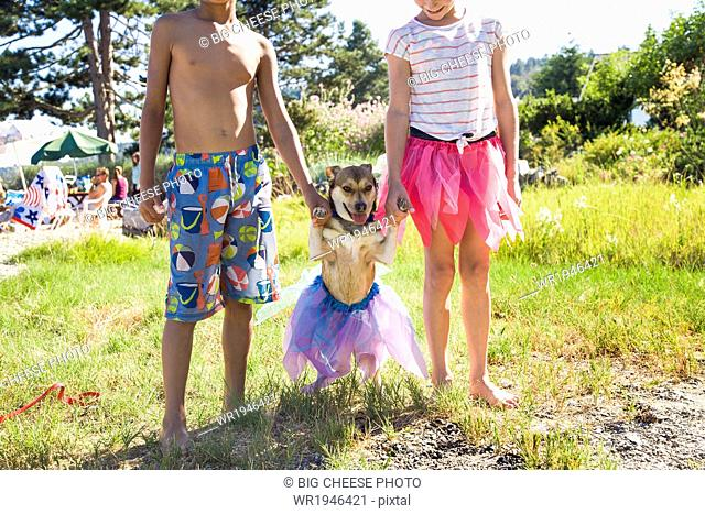 Small dog in a tutu with his paws held up by children