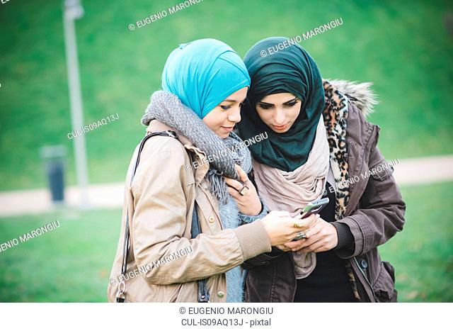 Two female friends in park reading text on smartphones