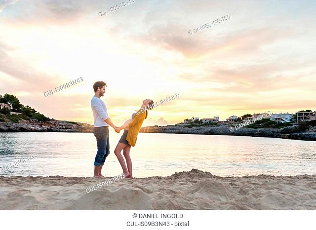 Pregnant woman and man face to face on beach, holding hands, laughing