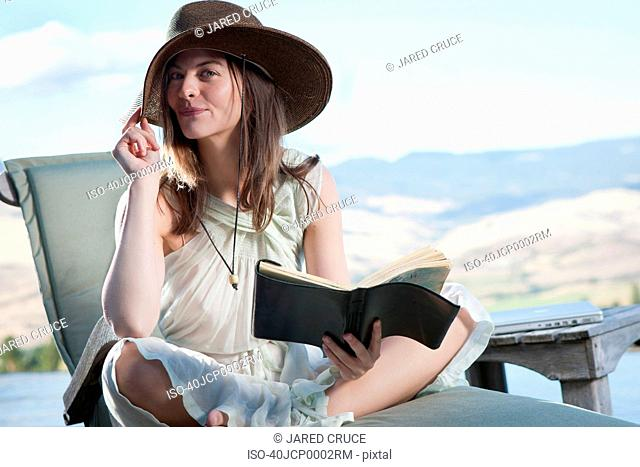 Smiling woman reading book outdoors