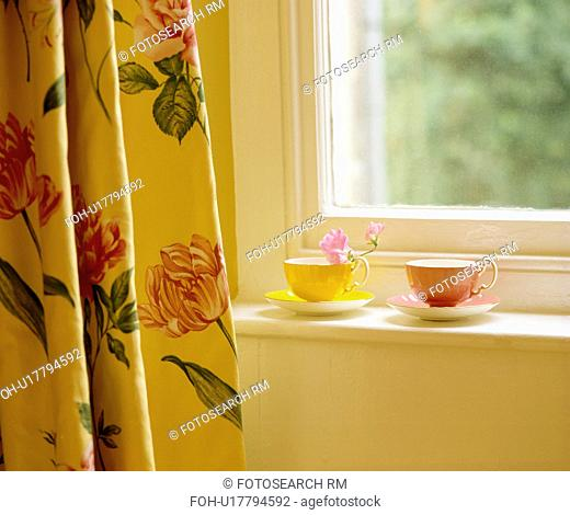 Close-up of tulip-patterned curtain beside window with yellow and pink cups on sill