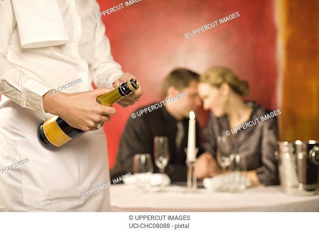 Waitress opening bottle of champagne