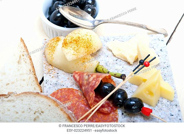 cold cut assortment cheese salami and fresh pears served on a granite stone