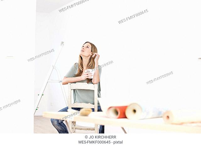 Woman sitting on chair with cup, wallpaper on table in foreground