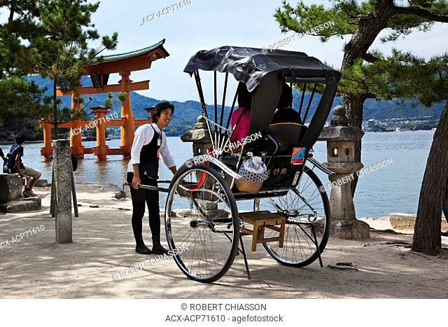 Smiling runner talking with tourists seated in his rickshaw on Miyajima Island, Japan. In the background is the gate, or torii