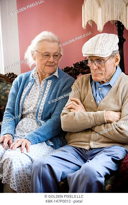 Senior couple in contemplation while sitting on sofa in livin groom