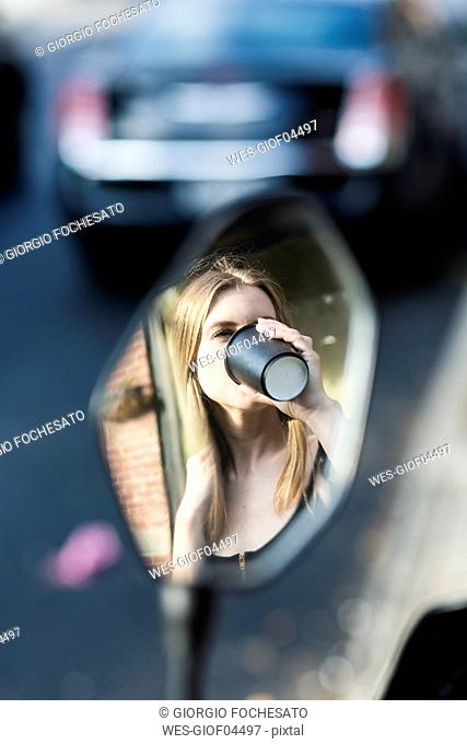 Young woman drinking coffee to go, mirror image