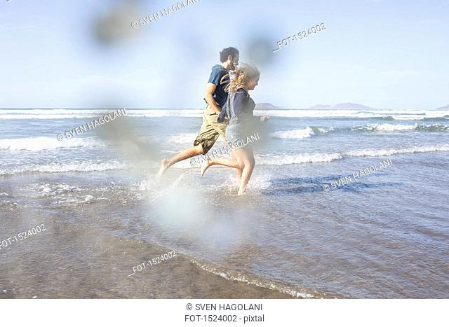 Side view of happy couple running towards sea