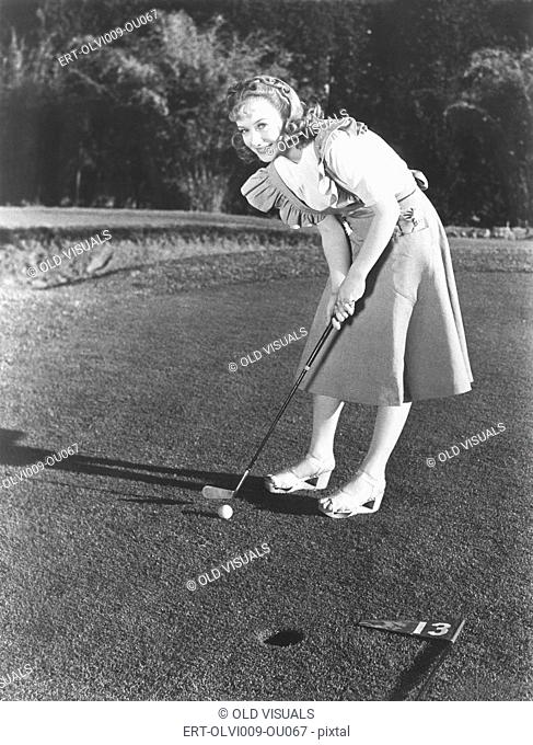 Female golfer about to take a shot