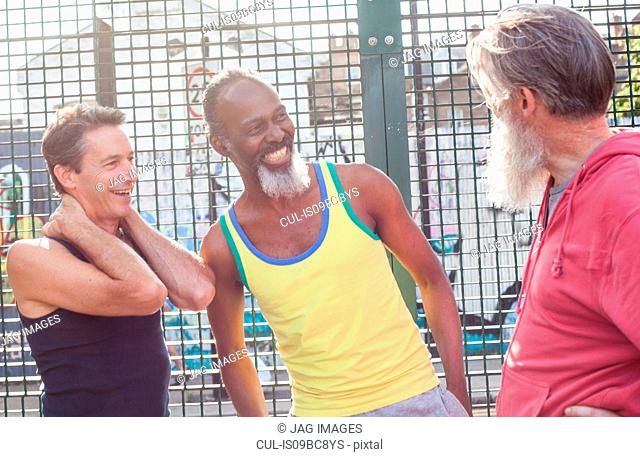 Three mature men in basketball court, laughing together