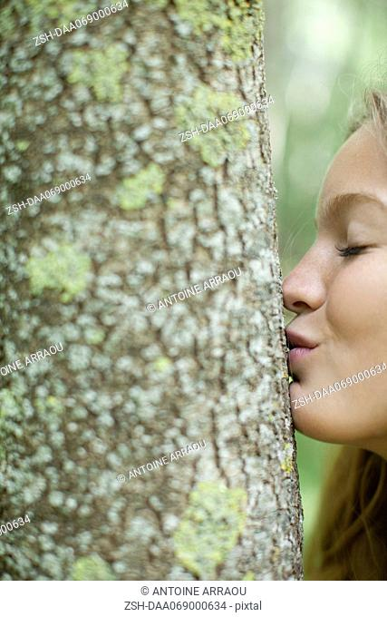 Young woman kissing tree