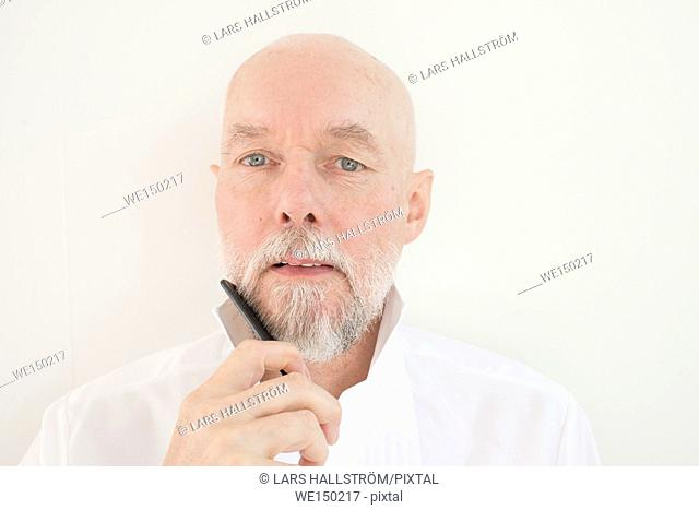 Old man combing beard and mustache with comb. Serious senior adult taking care of his facial hair