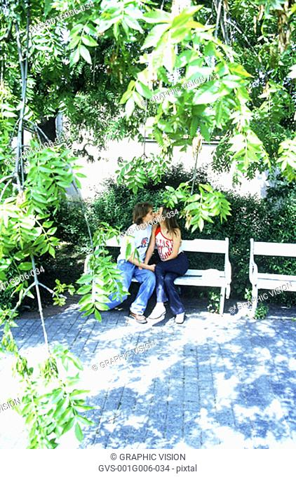 Young couples kissing on a park bench