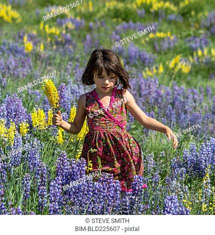Caucasian girl holding bouquet on hillside with wildflowers