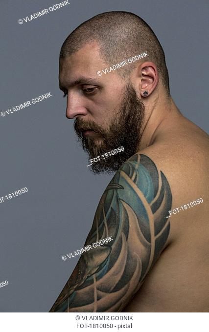 Portrait serious man with beard and tattooed arm
