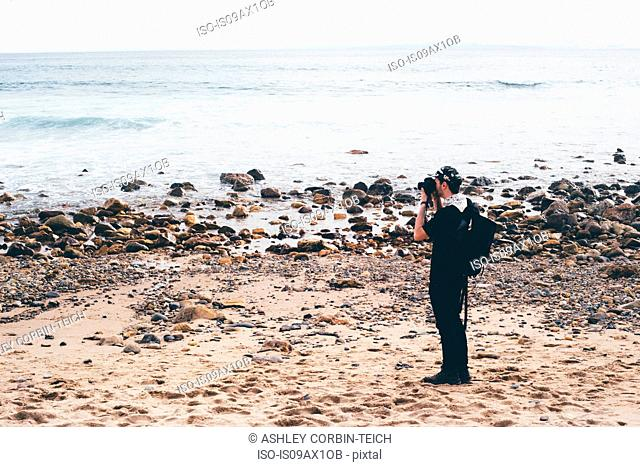Male photographer photographing from beach, Crystal Cove State Park, Laguna Beach, California, USA