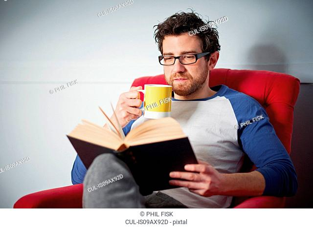 Mid adult man reading book on armchair