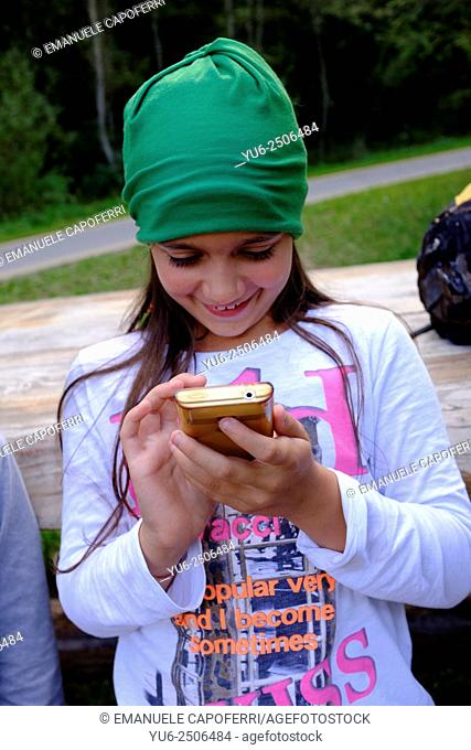 Little girl playing with smartphone at the park