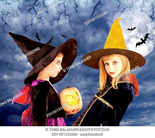 Halloween kid girls and pumpkin on cloudy moon sky
