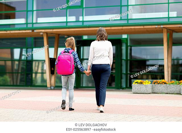 education, childhood, family and people concept - elementary student girl with mother going to school