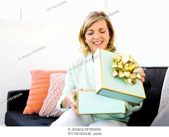 Mature woman opening gift