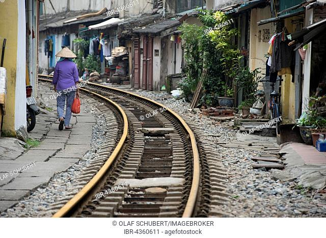 Woman with straw hat walking near train tracks, Hanoi, Vietman