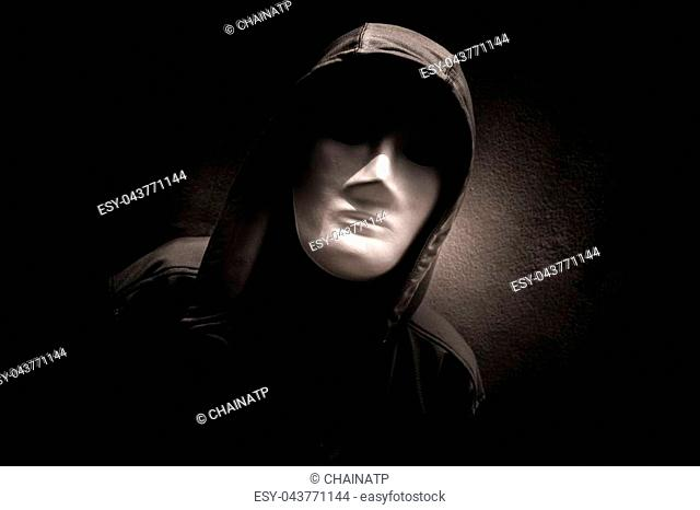 Mysterious woman wearing white mask under hoodie,Scary background for book cover