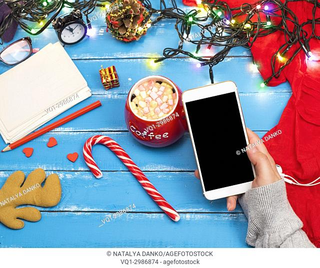 smartphone with a black screen in a woman's hand, next to a red cup of coffee with marshmallow, top view