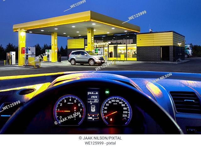 Car interior with windshield and illuminated gas station. Dashboard, instrument panel and speedometer, Electronic controls